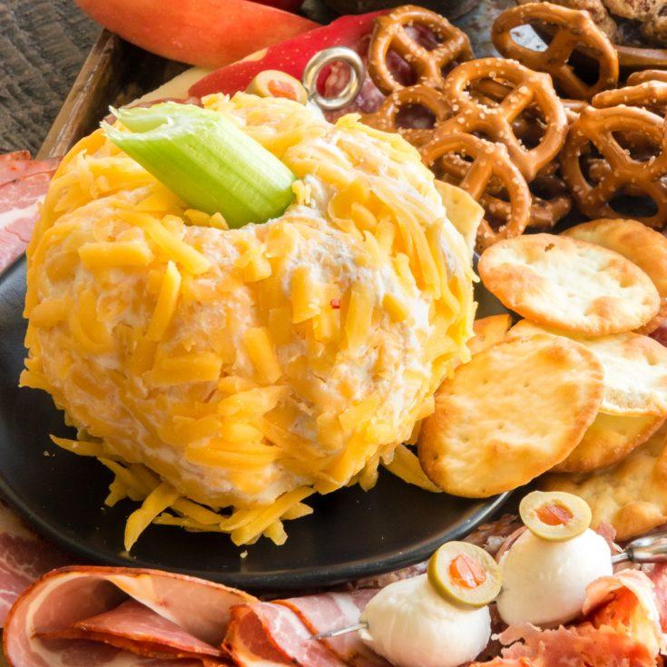 pumpkin shaped cheeseball all savory on a tray