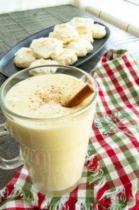 christmas napkin topped with mug of eggnog next to cookies