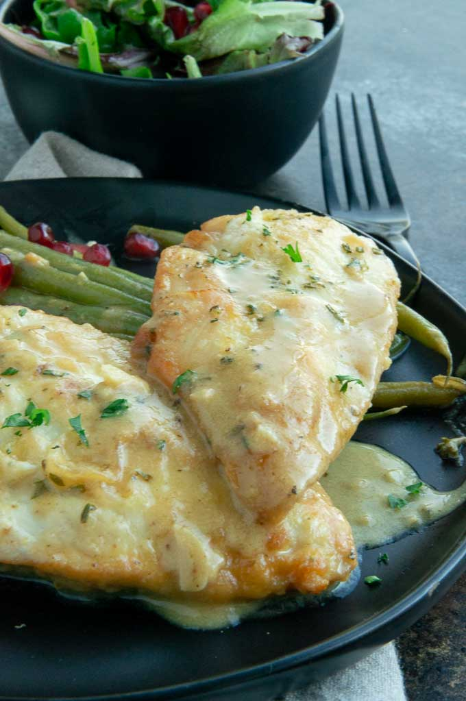 mustard chicken saute on a black plate with green beans