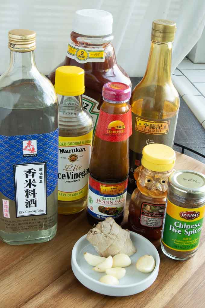 Chinese rice wine, rice wine vinegar, ketchup, soy sauce, garlic, ginger, chinese 5 spice and hoisin sauce on a tray