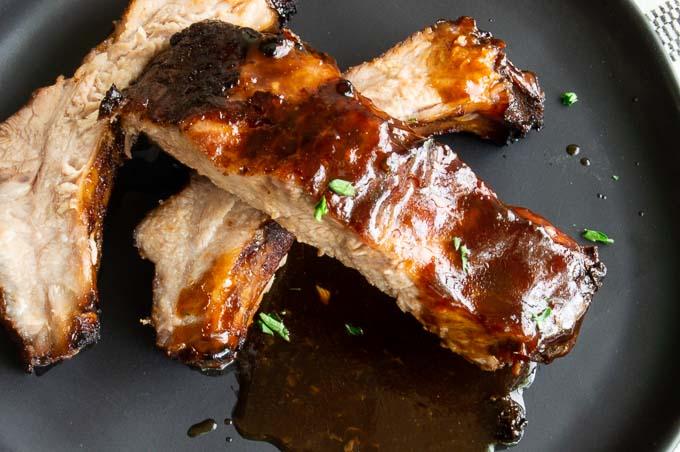 sticky sauce laden ribs on a black plate