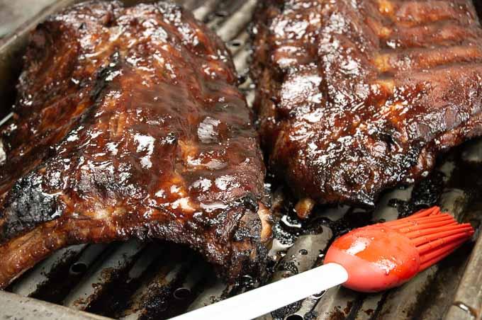 rib racks with bbq sauce on a broiler pan