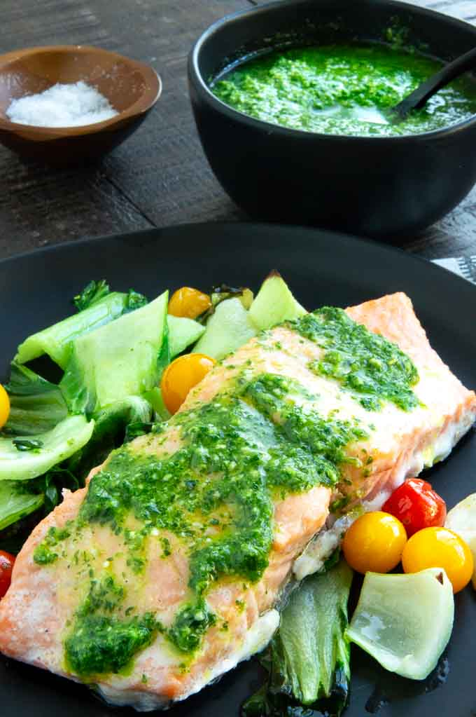 bowl of pesto being served next to the salmon on a dinner plate