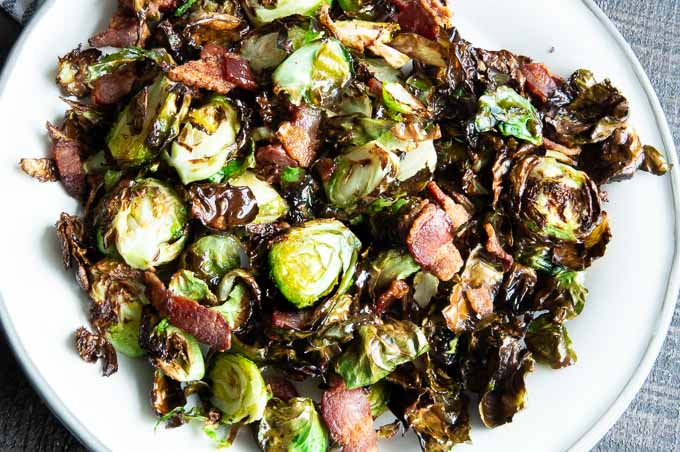 Crispy, roasted brussel sprouts on a white plate