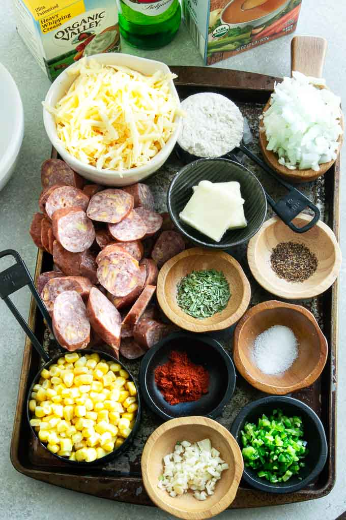 All of the ingredients for beer brat corn chowder on a tray- Cheese, brats, corn, flour, garlic, jalapeno, onion, salt, pepper,oregano, paprika