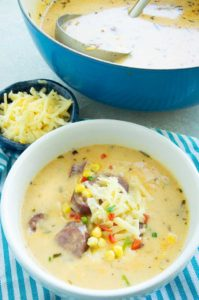 heart bowl of corn chowder topped with cheese and bratwurst on the table