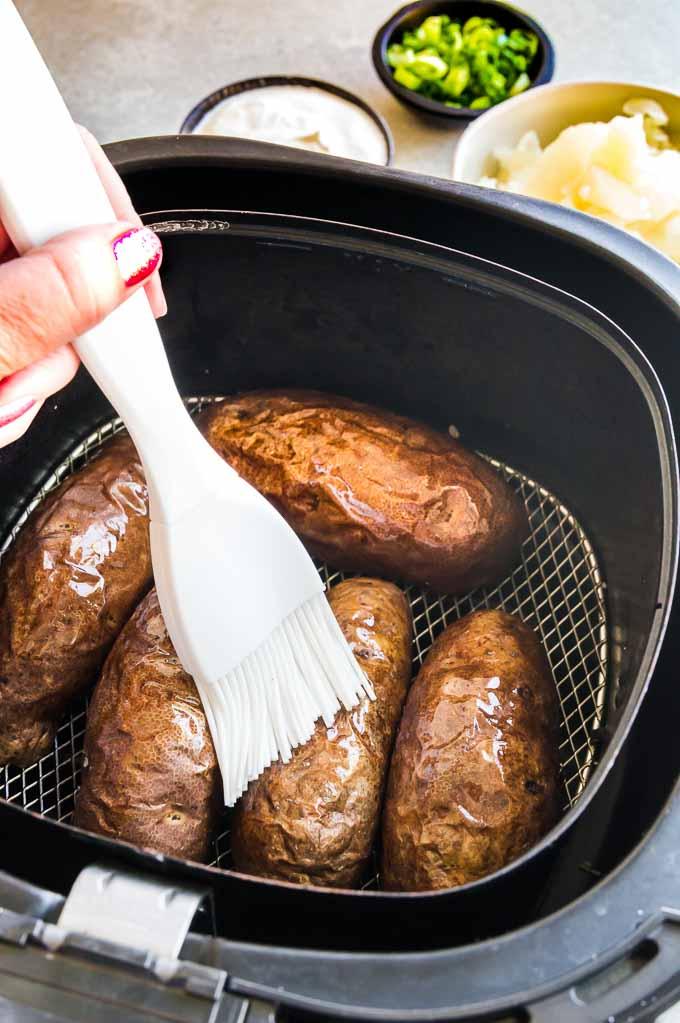 brushing the potato skin in the air fryer