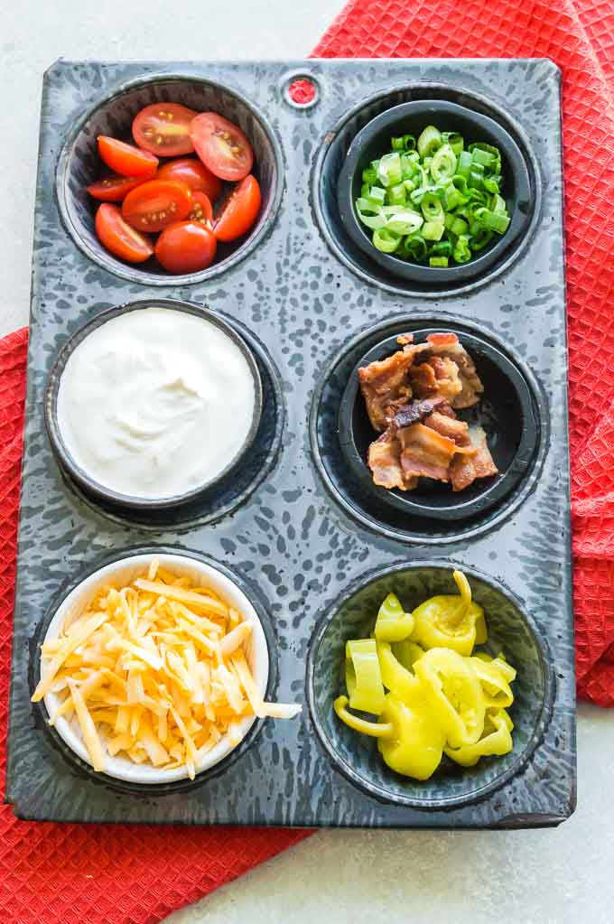 Muffin tin with toppings for potato skins