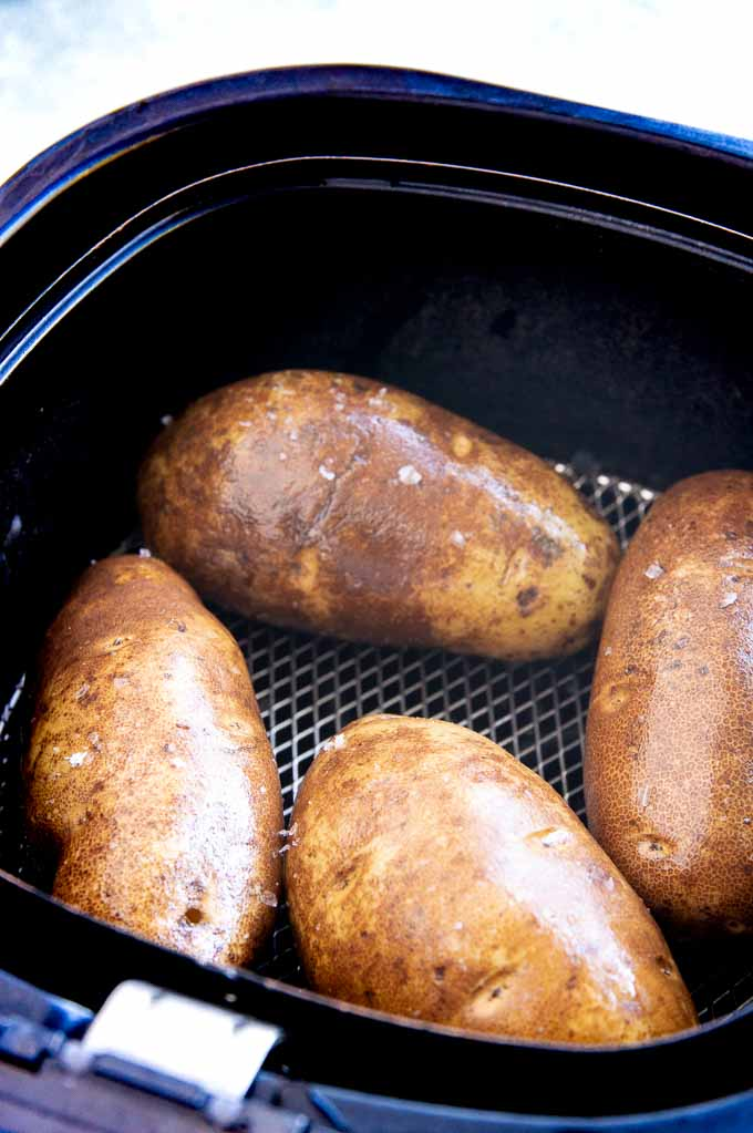 Russet potatoes in the basket of an air fryer