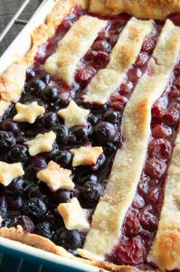 closeup of baked stars, strips on top of cherry pie fillig