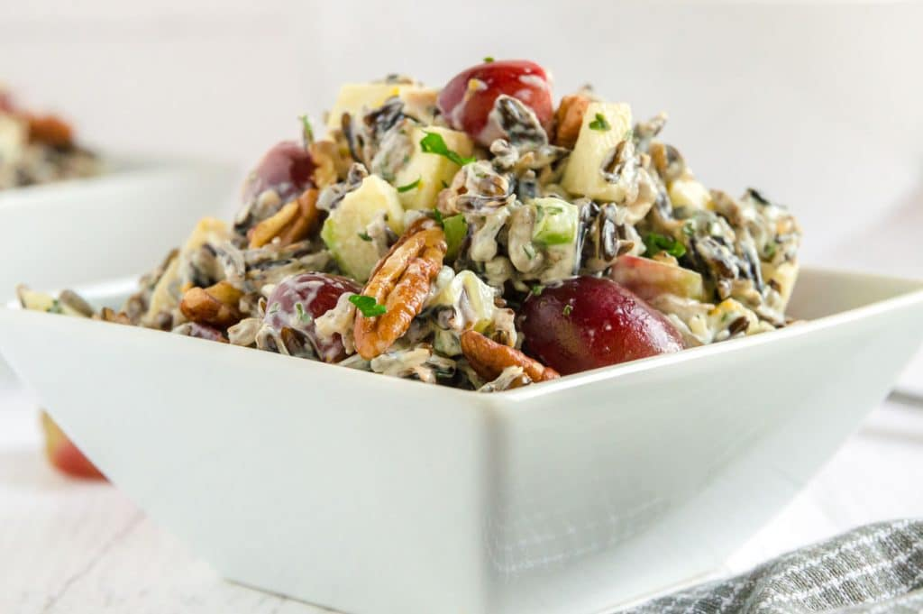SQUARE white bowl with rice, grapes and pecans in it