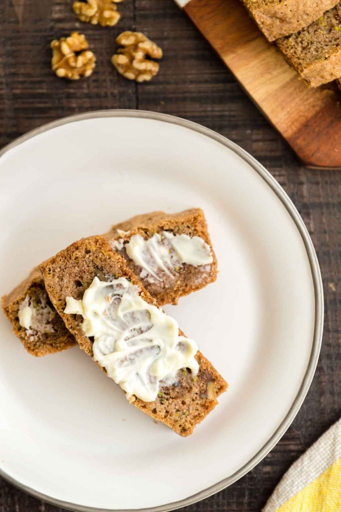 Zucchini bread with butter slathered over the top of it on a plate