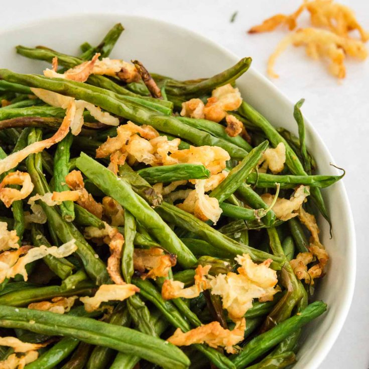 close up of green beans in a bowl with onions on top