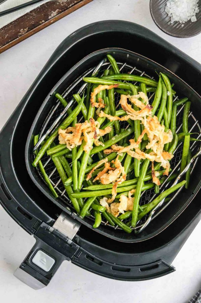 onions topping the green beans in the air fryer
