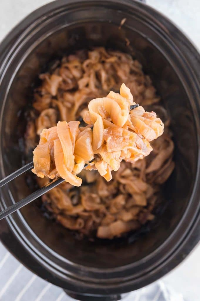 freshly caramelized onion from the slow cooker on  tongs