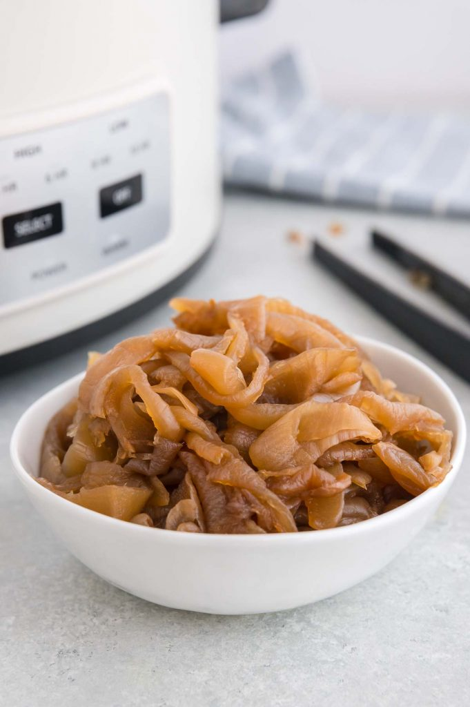bowl of slow cooked onions in front of crock pot