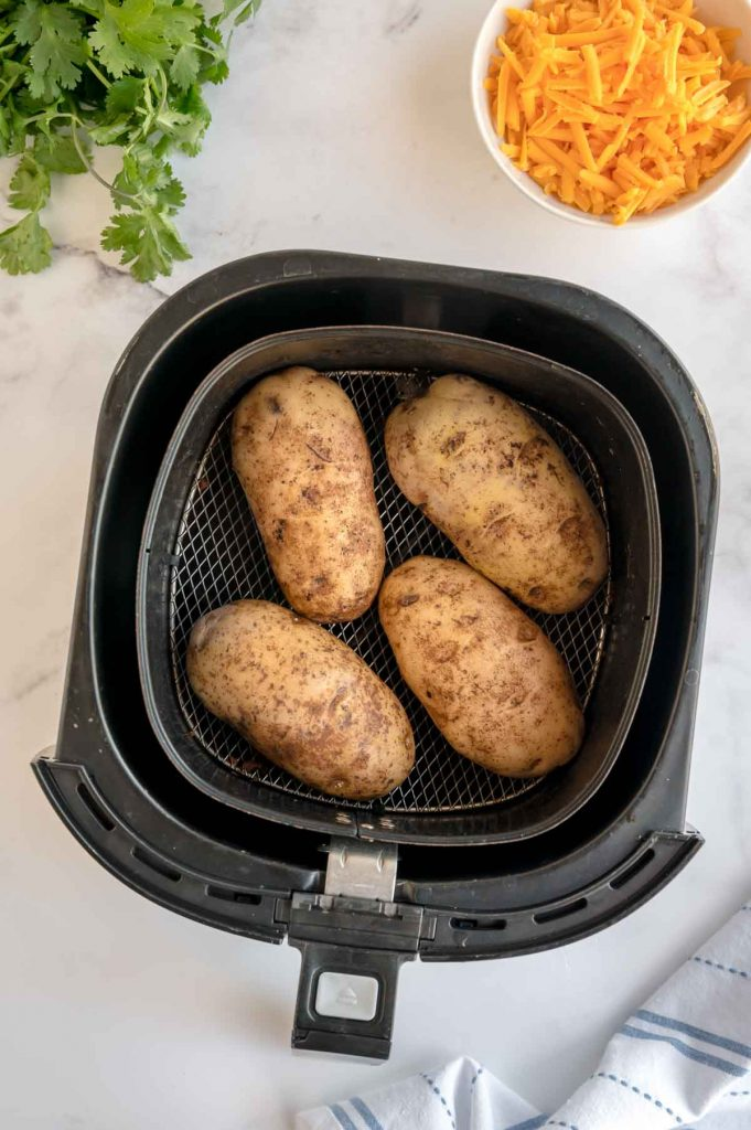 air fryer full of baked potatoes