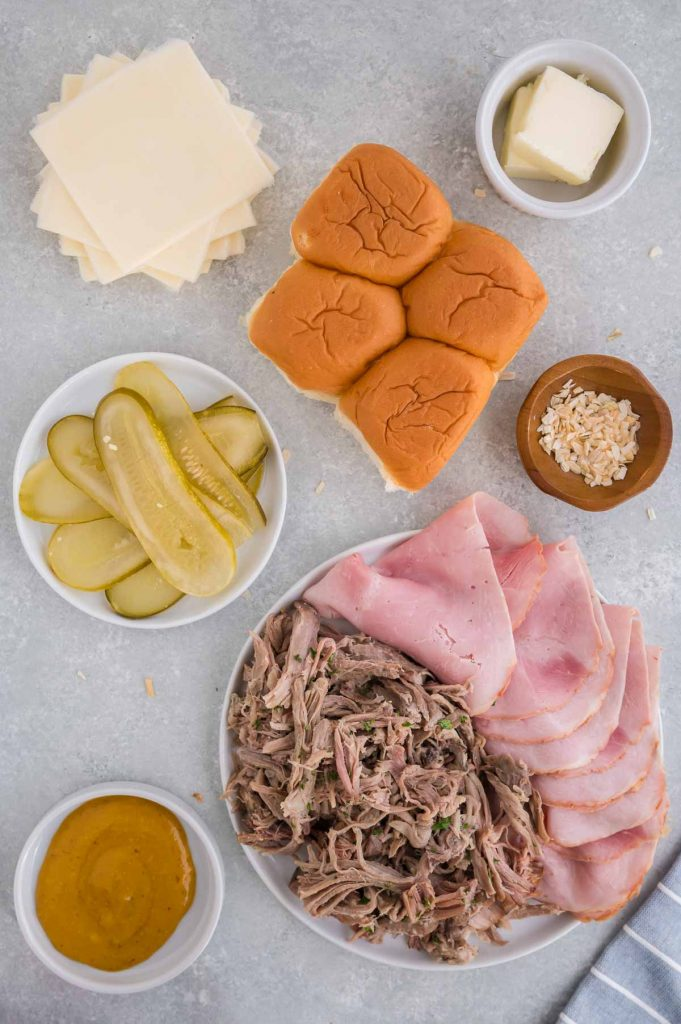 ham, pork, rolls, cheese, butter, mustard and onion for making Cuban sandwiches on a tray