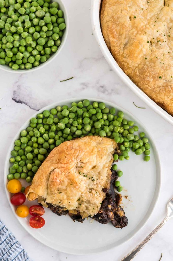 tabletop serving of guinnes pie and a bowl of peas