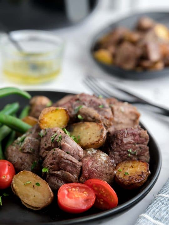 Steak bites and potatoes on a black plate with an air fryer in the background