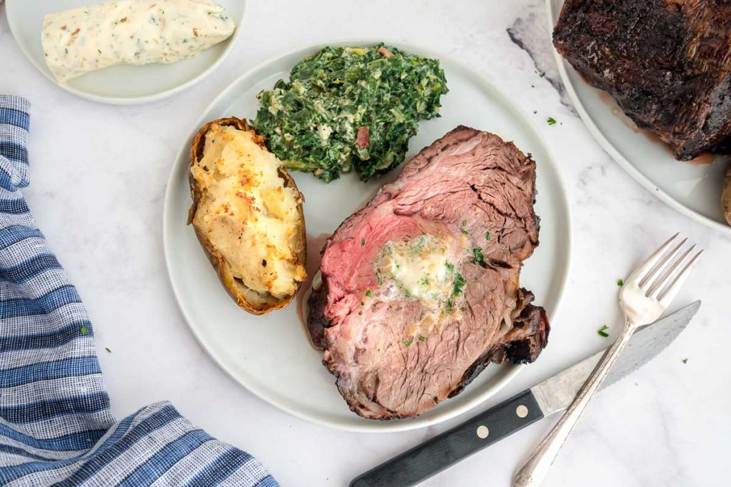 dinner plate with prime rib, potatoes and spinach