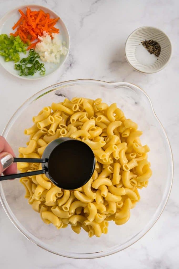 pouring vinegar into warm pasta