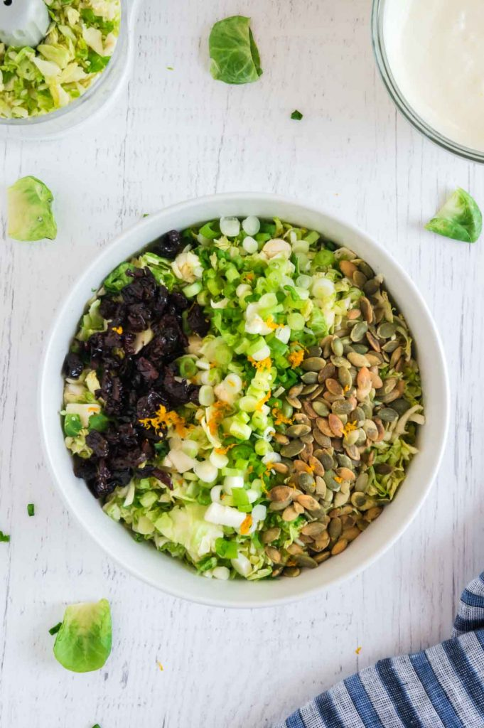 Slaw topped with green onions, nuts and dried cherries