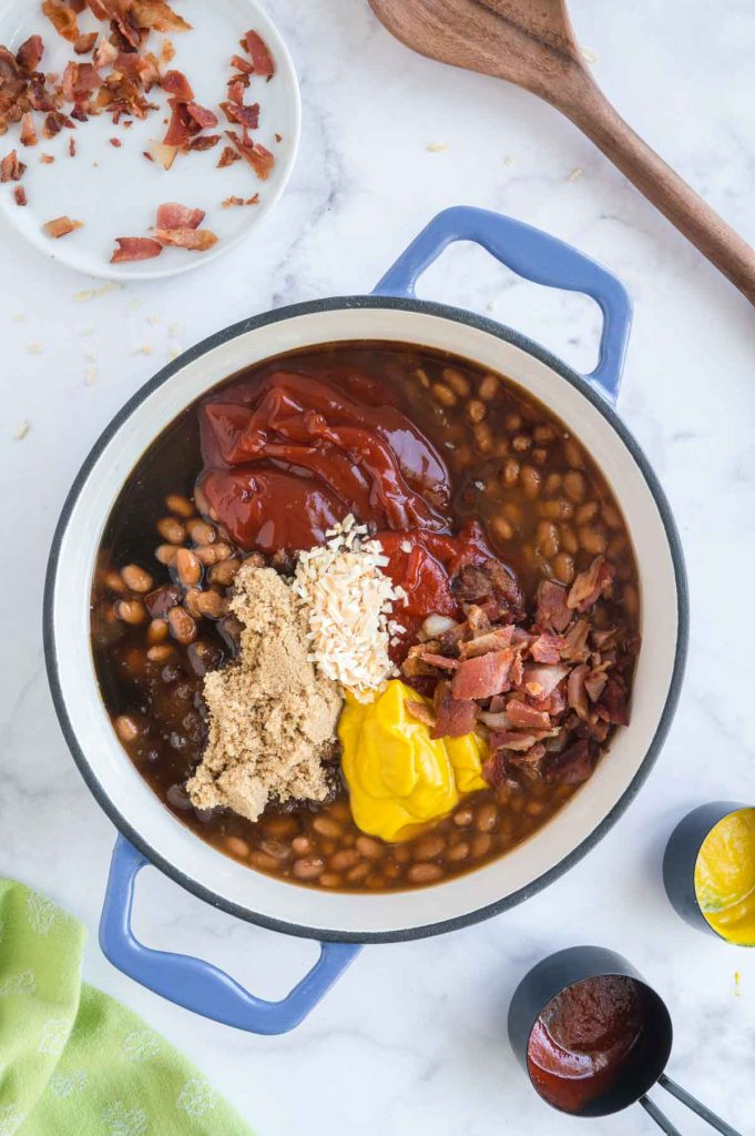 all ingredients on top of canned beans in a pot