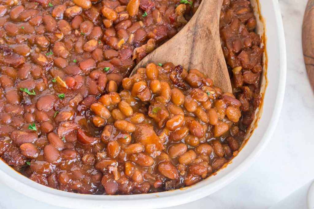 serving dish of baked beans from a can that are doctored