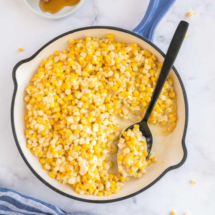 cast iron pan full of honey butter corn