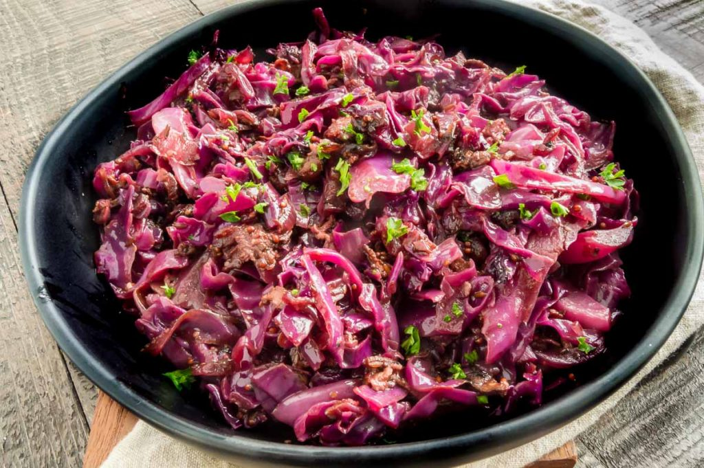 black bowl with red cabbage in it alone on a table