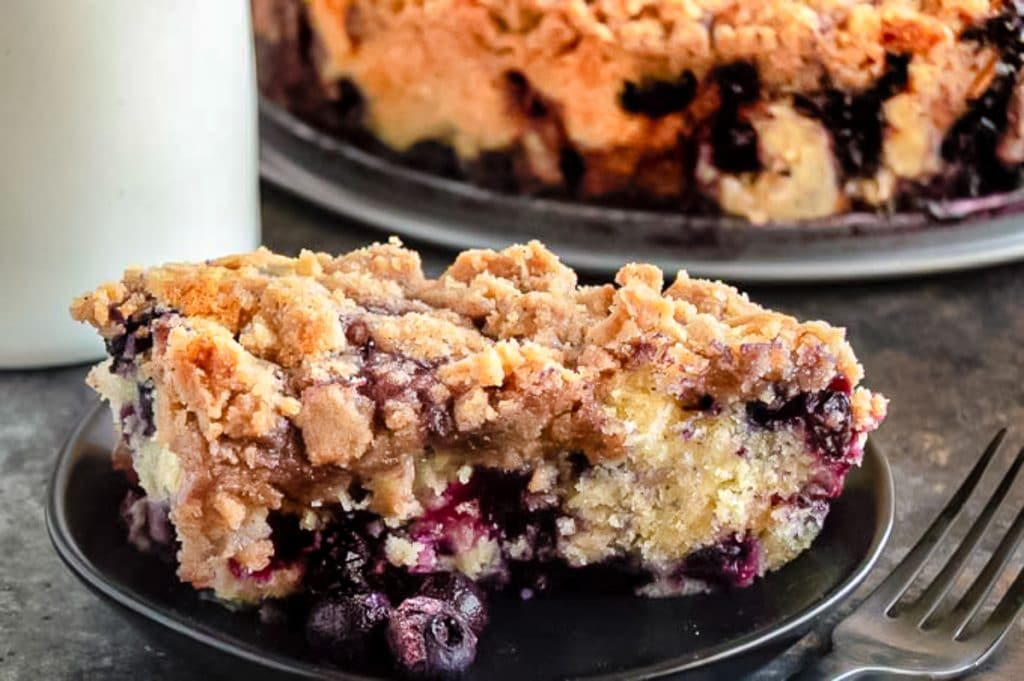 slice of blueberry buckle cake on a black plate next to coffee